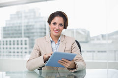 Businesswoman smiling and holding her tablet pc Royalty Free Stock Photo