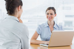 Businesswoman smiling at interview candidate Stock Photo