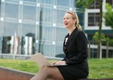 Businesswoman smiling with laptop outdoors Stock Images