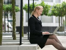 Businesswoman smiling with laptop outside Stock Photography
