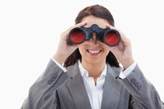 Businesswoman smiling and looking through binoculars Royalty Free Stock Photo
