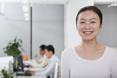 Businesswoman smiling in the office, coworkers in the background Royalty Free Stock Images