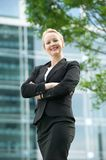 Businesswoman smiling outdoors with arms crossed Royalty Free Stock Photo