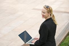 Businesswoman smiling outdoors with laptop Stock Images