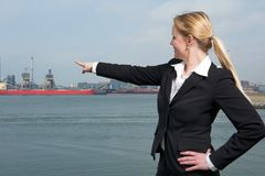 Businesswoman smiling outdoors and pointing finger at ships in harbor Stock Image