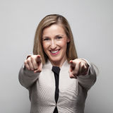 Businesswoman. Smiling businesswoman pointing using her fingers in a grey background Stock Photo