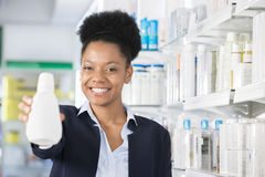 Businesswoman Smiling While Presenting Bottle In Drugstore Stock Image