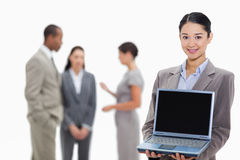 Businesswoman smiling showing a laptop screen. Close-up of a businesswoman smiling showing a laptop screen with co-workers talking in the background Stock Photography