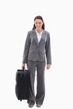 Businesswoman smiling with a suitcase. Against white background Royalty Free Stock Image