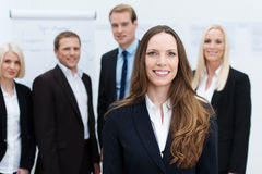 Businesswoman smiling with a team behind her Royalty Free Stock Image