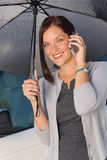 Businesswoman smiling under umbrella call phone Royalty Free Stock Photography