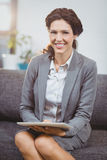 Businesswoman smiling while using digital tablet in office Stock Image