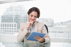 Businesswoman smiling and using her digital tablet Royalty Free Stock Images