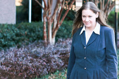 Businesswoman Smiling While Walking. Businesswoman In Front Of Corporate Office Buildings Stock Image