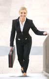 Businesswoman smiling and walking upstairs with briefcase Royalty Free Stock Photos