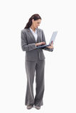 Businesswoman smiling while watching her laptop. Against white background Royalty Free Stock Photos