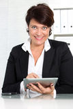 Businesswoman smiling while working Stock Image