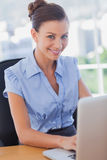 Businesswoman smiling and working on her laptop Stock Images