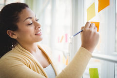 Businesswoman smiling while writing on adhesive note Royalty Free Stock Photography