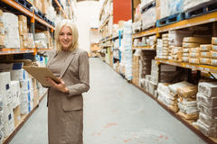 Businesswoman smiling while writing on a clipboard Royalty Free Stock Image