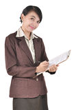Businesswoman smiling and writing on a folder Stock Photo