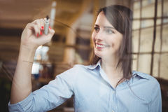 Businesswoman smiling while writing on glass with marker pen Royalty Free Stock Image