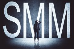 Businesswoman with SMM. Businesswoman with creative SMM text on concrete background. Social media and advertising concept royalty free stock photos