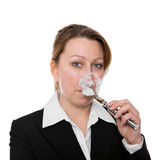 Businesswoman smokes an electric cigarette Royalty Free Stock Photography