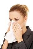 Businesswoman with sneezing into tissue. Royalty Free Stock Image