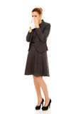 Businesswoman with sneezing into tissue. Stock Images
