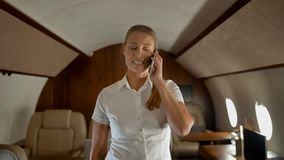 Businesswoman speaking about business by phone in middle of cabin. stock footage
