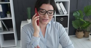 Businesswoman speaking on mobile phone. Young businesswoman speaking on mobile phone at office stock footage