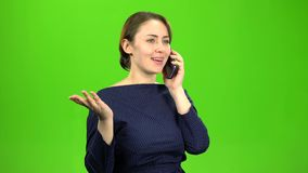 Businesswoman speaks on the phone and is angry with the interlocutor. Green screen. Businesswoman speaks on the phone and is angry with the interlocutor, she stock footage