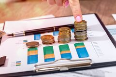 Businesswoman stacking euro coins on business graph.  Royalty Free Stock Photos