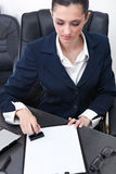Businesswoman stamping documents. Young businesswoman sitting at the desk in office and stamping document Stock Photography