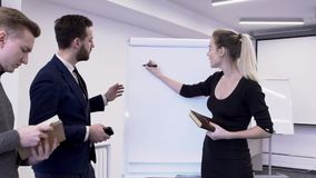 Businesswoman stand on white sheet picks chart, which colleagues look at for study. stock video