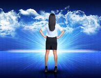 Businesswoman standing against blue landscape with. Businesswoman standing akimbo against digitally generated spacy blue landscape with rising sun and cloudy sky Stock Photo