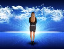 Businesswoman standing against blue landscape with. Businesswoman standing against digitally generated spacy blue landscape with rising sun and cloudy sky Royalty Free Stock Photos