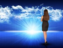 Businesswoman standing against blue landscape with. Businesswoman standing against digitally generated spacy blue landscape with rising sun and cloudy sky Stock Image