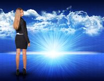 Businesswoman standing against blue landscape with. Businesswoman standing against digitally generated spacy blue landscape with rising sun and cloudy sky Stock Images