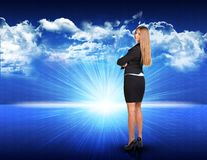 Businesswoman standing against blue landscape with. Businesswoman standing against digitally generated spacy blue landscape with rising sun and cloudy sky Royalty Free Stock Photo