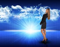 Businesswoman standing against blue landscape with Royalty Free Stock Photography