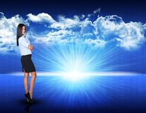 Businesswoman standing against blue landscape with. Businesswoman standing against digitally generated spacy blue landscape with rising sun and cloudy sky Royalty Free Stock Photography