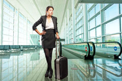Businesswoman standing at the airport. Businesswoman with a suitcase standing in front of the airport travelator Stock Photos