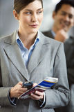 Businesswoman standing in airport terminal, holding mobile phone and ticket, making sideways glance Stock Images