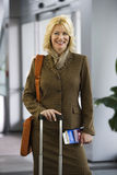Businesswoman standing in airport terminal with luggage and ticket, smiling, front view, portrait Stock Photo