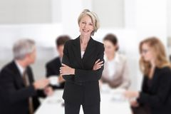 Businesswoman Standing With Arms Crossed In Boardroom Stock Images
