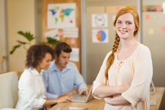 Businesswoman standing with arms crossed while colleagues working on laptop Stock Image