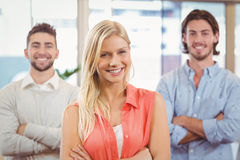 Businesswoman standing with arms crossed with male colleagues Stock Image