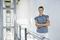 Businesswoman Standing Arms Crossed In Office Corridor Stock Photos